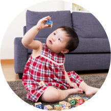 infant sitting on the floor playing